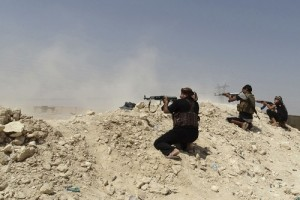 Tribal fighters fire their weapons during an intensive security deployment in Haditha